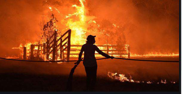 RESIDENTS DEFEND A PROPERTY FROM A BUSHFIRE AT HILLSVILLE NEAR TAREE 350 KILOMETERS 217 MILES NORTH OF SYDNEY ON NOVEMBER 12 2019. A STATE OF EMERGENCY WAS DECLARED ON NOVEMBER 11 AND